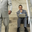 Businessman sitting on steps with laptop — Stock Photo