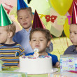 Boy blowing out birthday candles at party with friends - Stock Photo