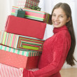 Stock Photo: Portrait of teenager holding stack of gifts in front of Christmas tree