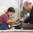 Elderly man and grandson playing with toy dinosaurs - Stock Photo
