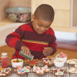 Young boy making gingerbread men — Stock fotografie