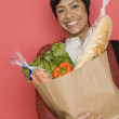 Portrait of woman holding bag of groceries — Stock Photo