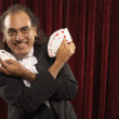 Portrait of magician with cards fanned in hand - Stock Photo