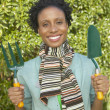 Young woman holding gardening tools and smiling for the camera — Stock Photo