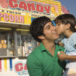 Young girl kissing her father at a carnival — Foto Stock