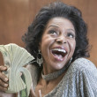 Close up of African American woman holding stack of 100 dollar bills — Stock Photo