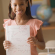 Stock Photo: Young girl showing off test score of 100