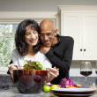 Couple making salad in kitchen — Stock Photo