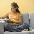 Teenage girl sitting on couch doing homework — Stock Photo