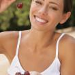 młoda kobieta uśmiechając się z wiśniami — Zdjęcie stockowe