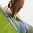 Stock Photo: Close up of hand carrying shopping bags
