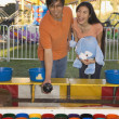 Couple playing with fairground attraction — Stock Photo #23237980