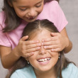 Girl with hands over another girl's face — Stok fotoğraf