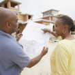 African American couple reading house plans at construction site — Stok fotoğraf