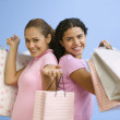 Portrait of two teenage girls holding gift bags — Stock Photo