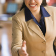 Businesswoman reaching out to greet camera — Stock Photo