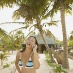 Junge Frau lacht während des Sprechens auf ihrem Handy — Stockfoto