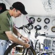 Stock Photo: Man repairing bike in bike shop