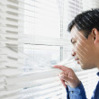 Man looking through office blinds - Stock Photo