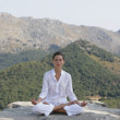 Young woman meditating on ledge — Stock Photo