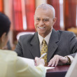 Businessman smiling at receptionist — Stock Photo