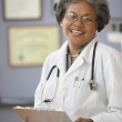 Portrait of mature female doctor holding chart — Stock Photo