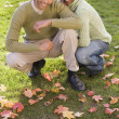 Portrait of couple kneeling in park - Stock Photo