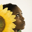Young woman holding a sunflower by her face - Foto Stock
