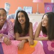 Three girls laying on bed - Stock Photo
