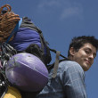 Low angle portrait of man carrying backpack and equipment - Foto Stock