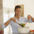 Young woman tossing a salad - Stock Photo