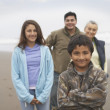 Portrait of family standing at beach - Stock Photo