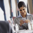 Businesswoman looking at her cell phone in a restaurant — Stock Photo