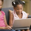 Young girls using a laptop together — Stock Photo