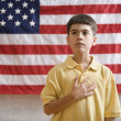 Stock Photo: Boy in front of Americflag with hand over heart