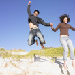 Stock Photo: Young couple jumping off a sand dune