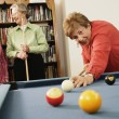 Elderly woman shooting pool - Stok fotoğraf