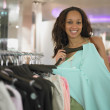 Young woman shopping for clothes - Stock Photo