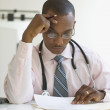 Male doctor reading paperwork with hand on head — Stock Photo