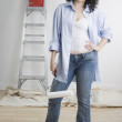 Portrait of woman with paint roller and ladder - Stock Photo