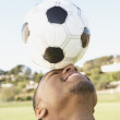 Portrait of soccer player balancing ball on forehead — Stock Photo