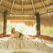 Young woman laying on bed in hut - Stock Photo