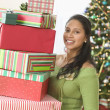 Portrait of woman holding stack of gifts in front of Christmas tree — Stok fotoğraf