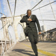 Blurred image of businessman running on bridge — Stock Photo