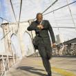 Blurred image of businessman running on bridge — Stock Photo #23239652