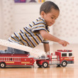 Young boy playing with fire truck — Stock Photo