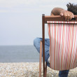 Man relaxing in lounge chair on beach — Stock Photo