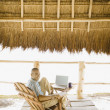 Young man using a laptop underneath thatch roof on the beach — Photo
