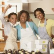 Portrait of three woman cheering while working in bakery — Stock Photo