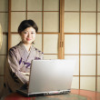Asian woman with computer — Stock Photo